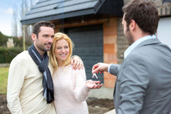 Real estate agent delivers keys to young atractive couple. View of a Real estate agent delivers keys to young atractive couple stock images