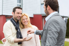 Real estate agent delivers keys to young atractive couple Stock Images