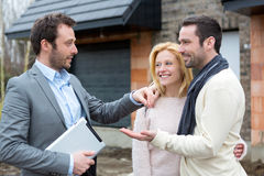 Real estate agent delivers keys to young atractive couple Stock Photos