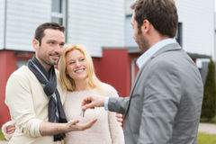Real estate agent delivers keys to young atractive couple Stock Photo