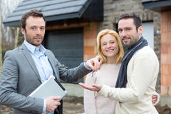 Real estate agent delivers keys to young atractive couple. View of a Real estate agent delivers keys to young atractive couple stock image