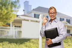 Real Estate Agent in Front of Blank Sign and House. Attractive Female Real Estate Agent in Front of Blank Real Estate Sign and House Royalty Free Stock Images