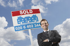 Real Estate Agent In Front Of Sold Sign And Cloudy Sky Stock Photo