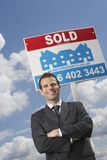 Real Estate Agent In Front Of Sold Sign And Cloudy Sky Royalty Free Stock Image