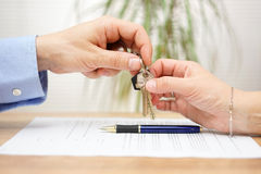 Real estate agent gives house keys to his client after signing c. Ontract Royalty Free Stock Image
