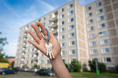 Real estate agent giving flat keys to a new property owner. On blurred background Royalty Free Stock Photo