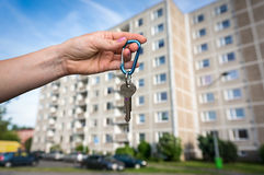 Real estate agent giving flat keys to a new property owner. On blurred background Royalty Free Stock Images