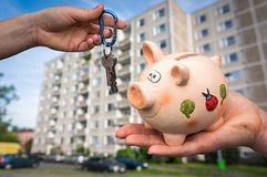Real estate agent giving flat keys to a new property owner. Who is paying last saving money from piggy bank on blurred background Royalty Free Stock Photo