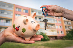 Real estate agent giving flat keys to a new property owner. Who is paying last saving money from piggy bank on blurred background Stock Image