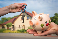 Real estate agent giving flat keys to a new property owner. Who is paying last saving money from piggy bank on blurred background Royalty Free Stock Photos