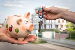 Real estate agent giving flat keys to a new property owner. Who is paying last saving money from piggy bank on blurred background Stock Photo