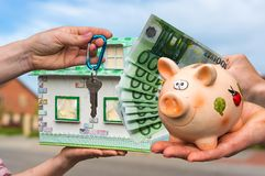 Real estate agent giving house key and model house to a new prop. Erty owner, who is paying by euro money from piggy bank on blurred background Royalty Free Stock Image