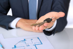 Real-estate agent giving  a house  key. The plan of a flat behind Royalty Free Stock Photo