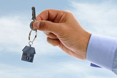 Real estate agent giving house keys. Estate agent holding out house keys on a silver house shaped keychain concept for moving, selling or buying a house Stock Image