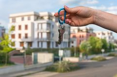 Real estate agent giving house keys to a new property owner. On blurred background Royalty Free Stock Photos