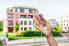 Real estate agent giving house keys to a new property owner. On blurred background Royalty Free Stock Photography