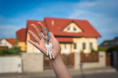 Real estate agent giving house keys to a new property owner. On blurred background Royalty Free Stock Images