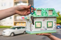 Real estate agent giving house keys to a new property owner, who. Is holding model house from paper on blurred background Royalty Free Stock Photos