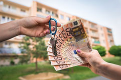 Real estate agent giving house keys to a new property owner. Who is paying by euro money on blurred background Royalty Free Stock Photo
