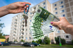 Real estate agent giving house keys to a new property owner. Who is paying by euro money on blurred background Royalty Free Stock Photos