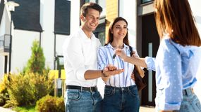 Free Real Estate Agent Giving House Keys To Young Couple Stock Photography - 163002022
