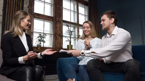 Real estate agent giving key from the new house, flat to the clients couple. stock footage
