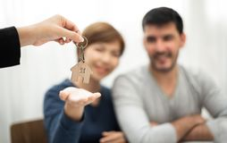 Real Estate Agent giving key of new house to Young couple. Happy men and women smiling stock photos