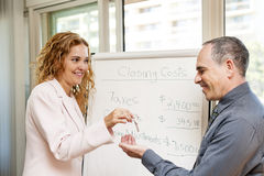 Real estate agent giving keys to client. Female real estate agent giving keys to new home buyer stock image