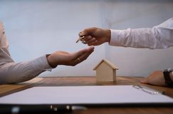 Real estate agent giving keys to customer after contract signature. royalty free stock image
