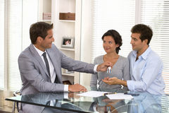 Real-estate agent giving keys to new property owners stock photo