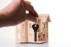 Real estate agent hand holds a house key Stock Photo