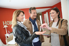 Real-estate agent handing keys of new home to clients. Real estate agent giving house keys to clients stock photography