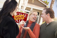 Real Estate Agent Handing Keys to Excited Couple Stock Photos