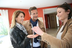 Real-estate agent handing keys to their clients. Real estate agent giving house keys to clients stock image