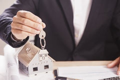 Real estate agent handing over house keys. Royalty Free Stock Image