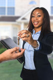 Real Estate Agent Handing Over Keys. African American real estate agent handing keys isolated over white background stock image