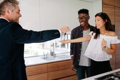 Estate agent handing over keys of new home to female buyer. Real estate agent handing over keys of new home to young couple. Happy new property owners with Royalty Free Stock Photo