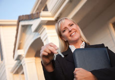 Real Estate Agent Handing Over Keys to New Home. Female Real Estate Agent Handing Over Keys in Front of Beautiful House Royalty Free Stock Images