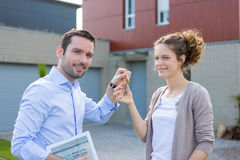 Real estate agent handing over keys. View of a Real estate agent handing over keys Stock Image