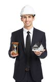 Real estate agent hands model house and hourglass. Real estate agent wearing white helmet hands model house and hourglass, isolated on white Royalty Free Stock Photo