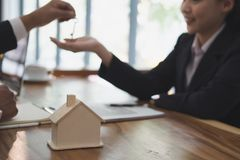 Real estate agent have a meeting with customer. sale & purchase. Property with house model, key and signing contract document. realtor talk with client Royalty Free Stock Photo