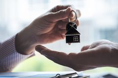 Real estate agent holding filing keys to customer after signing rental lease contract of sale purchase agreement stock photos