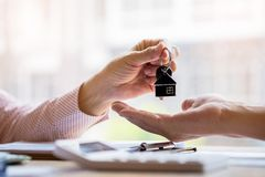 Real estate agent holding filing keys to customer after signing rental lease contract of sale purchase agreement stock image