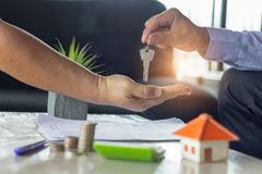 Real estate agent holding house key to his client after signing royalty free stock photography