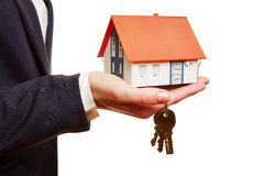 Real estate agent holding house and keys Royalty Free Stock Image