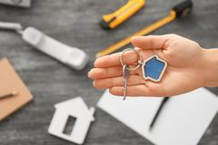 Real estate agent holding key with trinket. On blurred background Royalty Free Stock Image