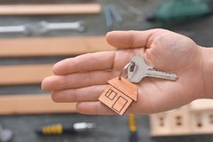Real estate agent holding key with trinket. On blurred background Royalty Free Stock Photo