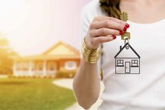 Real estate agent holding keys. In front of a beautiful new home royalty free stock photos