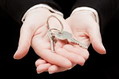 A real estate agent holding keys to a new house in her hands. Stock Photo