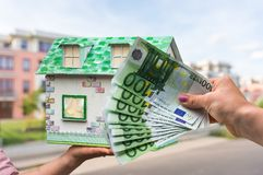 Real estate agent holding model house from paper and new propert. Y owner buying it by euro money on blurred background Royalty Free Stock Images